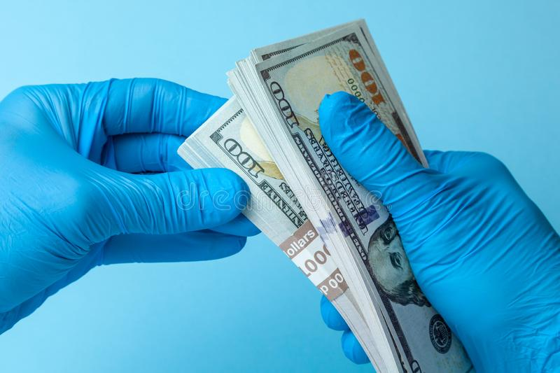 O doutor em luvas azuis guarda dólares do dinheiro do dinheiro no fundo azul Conceito do subôrno, da corrupção ou do salário fotos de stock royalty free