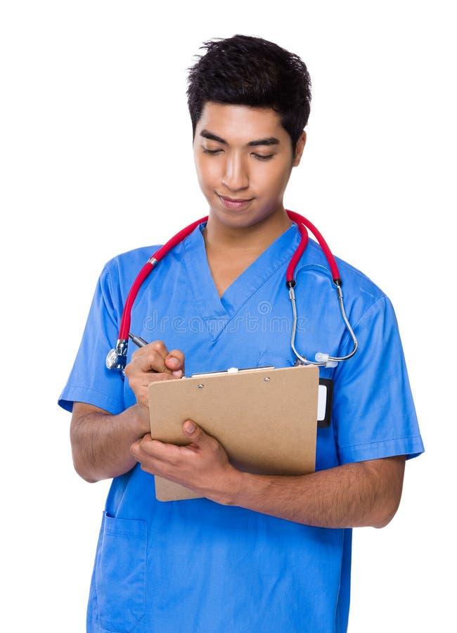 O doutor escreve na placa do arquivo foto de stock