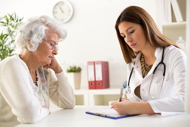 O doutor escreve a receita para o paciente superior da mulher fotos de stock royalty free
