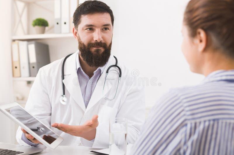 O doutor está consultando o paciente com a tabuleta digital foto de stock