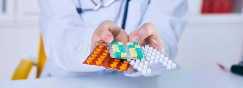 O doutor está dando comprimidos do analgésico a um paciente Apenas cede a tabela imagem de stock