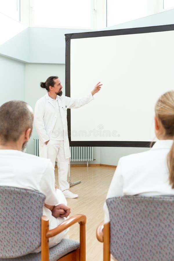 O doutor está estando na frente de um whiteboard vazio imagens de stock