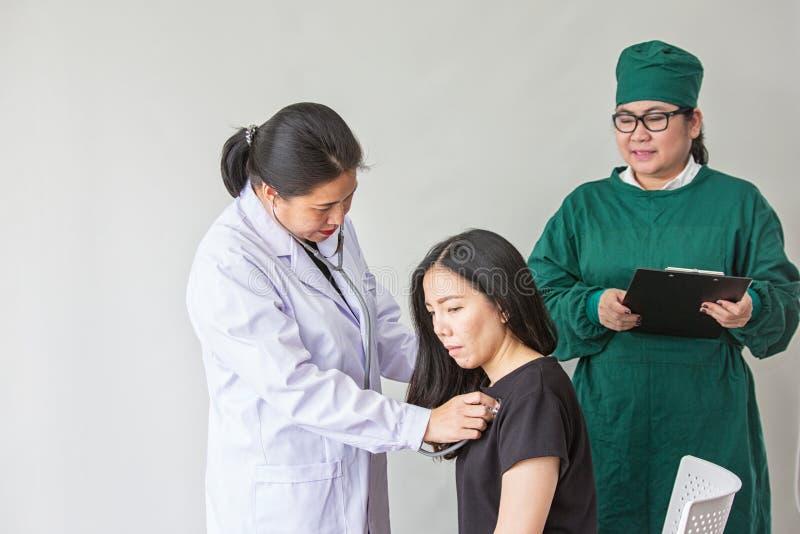 O doutor está medindo o pulso paciente do ` s Médico fêmea que examina seu paciente pressão sanguínea de medição do doutor do wom fotografia de stock royalty free