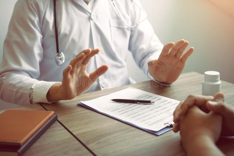 O doutor estava explicando sobre o tratamento ao paciente e disse-lhe para não se preocupar sobre ficar doente fotografia de stock