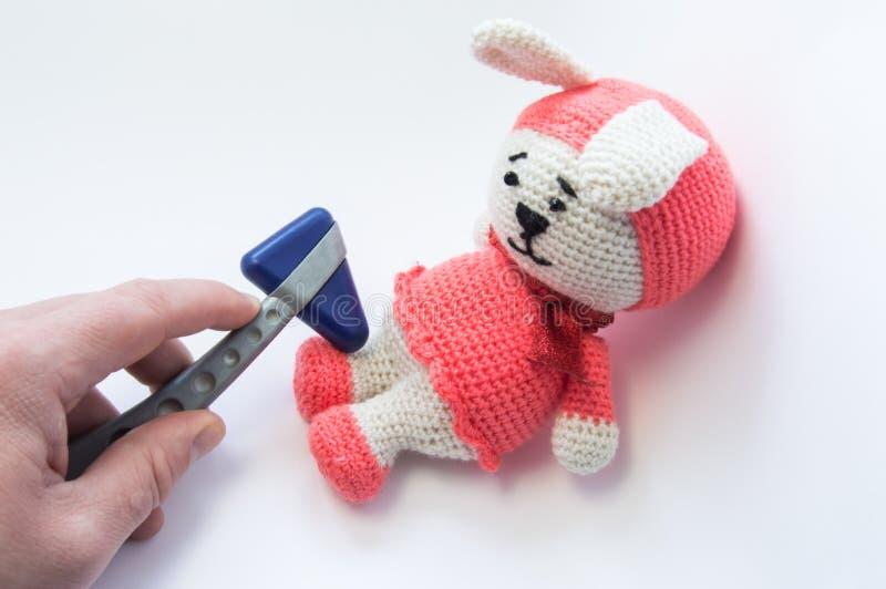 O doutor examina o brinquedo macio do coelho com reflexos neurológicos do martelo e das verificações nos pés Conceito para o exam imagem de stock royalty free