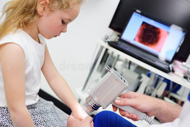 O doutor examina a criança especial das toupeiras do dispositivo médico imagens de stock