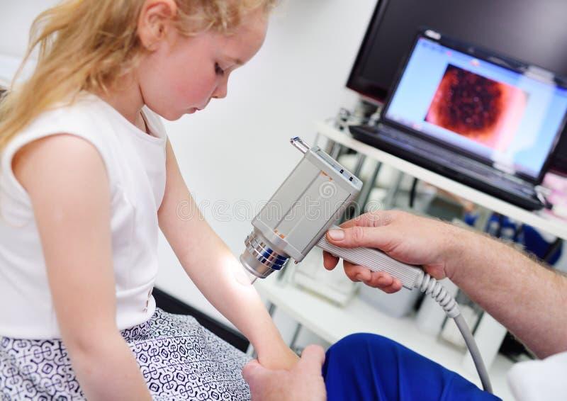 O doutor examina a toupeira paciente do ` s foto de stock