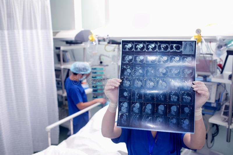 O doutor examina a varredura do CT do paciente em uma divisão de hospital fotografia de stock
