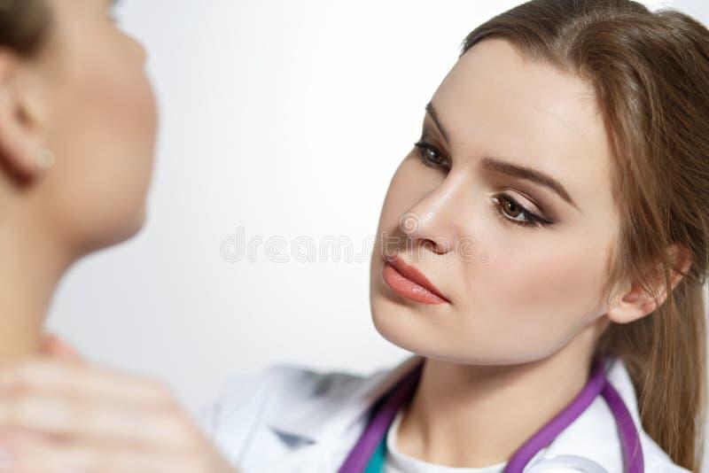 O doutor fêmea bonito da medicina com cara séria examina o patie imagem de stock