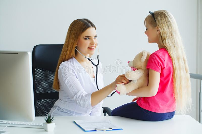 O doutor fêmea de sorriso dos jovens e seu paciente pequeno com peluche sejam fotos de stock royalty free