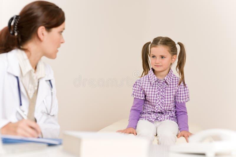 O doutor fêmea escreve a prescrição para a criança fotos de stock