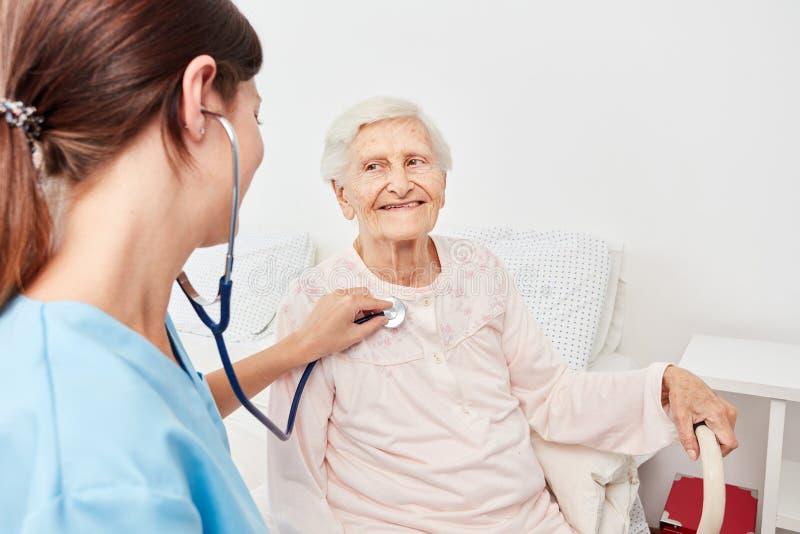 O doutor fêmea novo bate a mulher superior com estetoscópio fotos de stock royalty free
