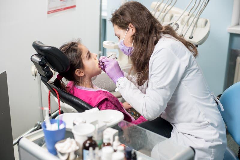 O doutor fêmea novo está tratando os dentes pacientes da menina no escritório dental da clínica Equipamento dental fotografia de stock royalty free