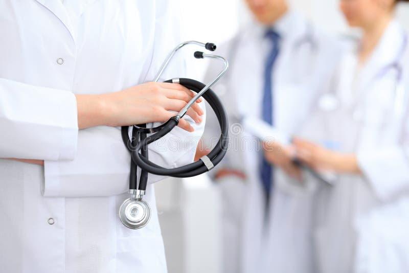 O doutor fêmea que guarda um estetoscópio em sua mão, três doutores está no fundo imagens de stock royalty free