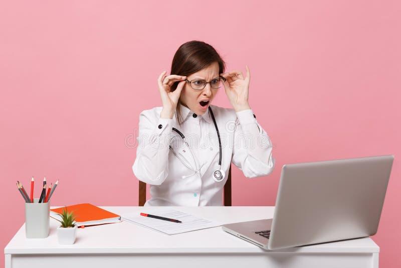 O doutor fêmea triste cansado senta-se no trabalho de mesa no computador com documento médico no hospital isolado na parede cor-d fotos de stock royalty free