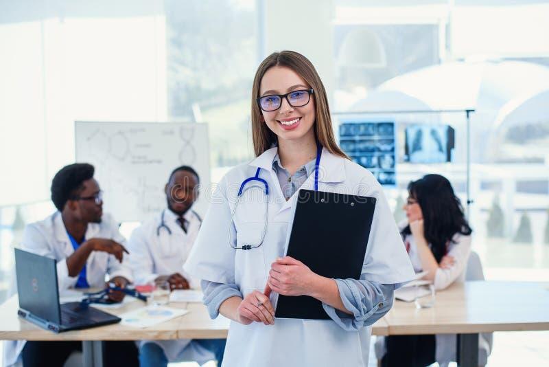 O doutor fêmea usa o tablet pc na sala de conferências do hospital Doutor fêmea profissional no uniforme médico branco em fotos de stock