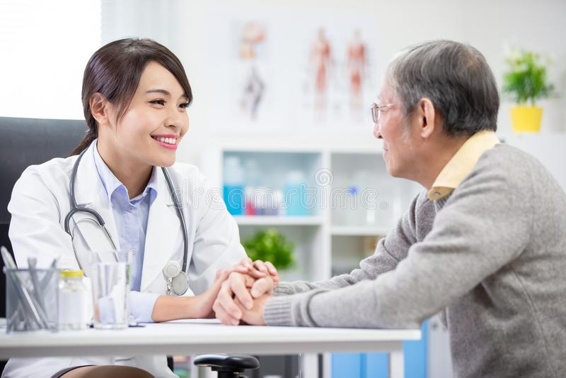 O doutor fêmea vê um paciente mais idoso fotografia de stock