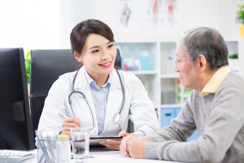 O doutor fêmea vê um paciente mais idoso fotografia de stock royalty free