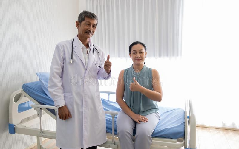 O doutor falou sobre a doen?a do paciente f?mea no hospital, o doutor falou com um sorriso para fazer o real paciente fotografia de stock