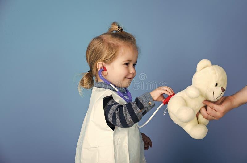 O doutor feliz do veterinário da criança examina o animal de estimação do brinquedo com estetoscópio fotografia de stock
