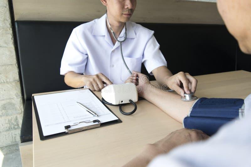O doutor fez um acordo com os pacientes com hipertensão manter a saúde foto de stock royalty free