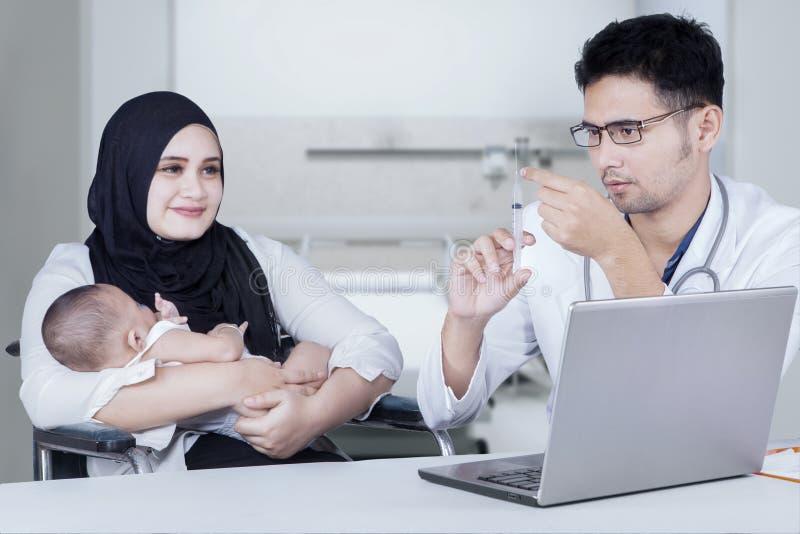 O doutor guarda a seringa para dar a vacina no bebê imagem de stock royalty free