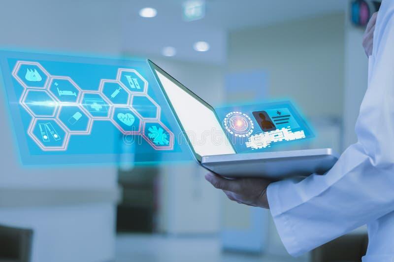 O doutor guarda um portátil à disposição no hospital, analisa sintomas do paciente para usar-se como a informação no tratamento d imagens de stock