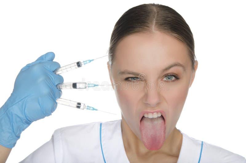O doutor mantém seringas e mostra a língua fotografia de stock