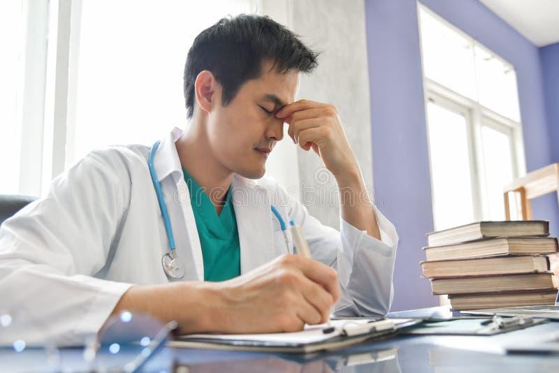 O doutor masculino asiático novo forçado está trabalhando foto de stock