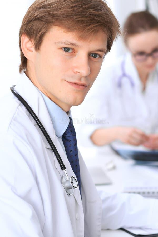 O doutor masculino desconhecido está sentando-se na tabela e está trabalhando-se no escritório do hospital Close up do estetoscóp fotografia de stock