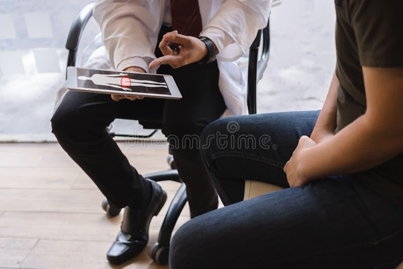 O doutor masculino e a paciente que sofre de câncer testicular estão discutindo sobre o relatório de teste do câncer testicular C fotografia de stock