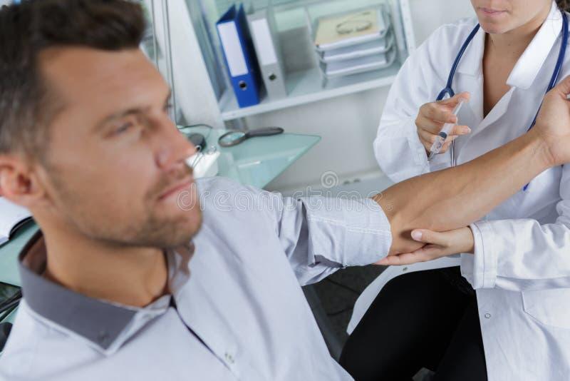 O doutor masculino que injeta pacientes arma-se no escritório médico foto de stock