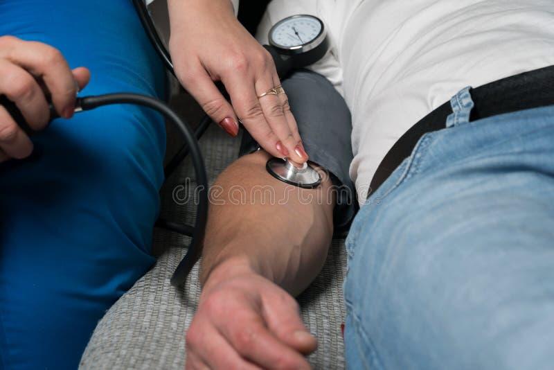 O doutor mede a pressão do paciente em casa foto de stock