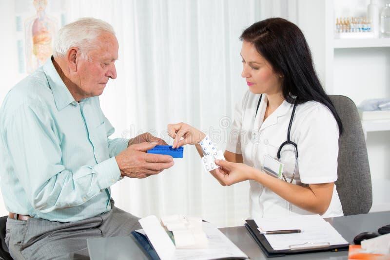 O doutor mostra ao paciente como usar comprimidos diários da dose foto de stock