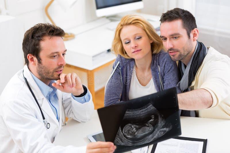 O doutor mostra um ultrassom a um par feliz novo fotos de stock