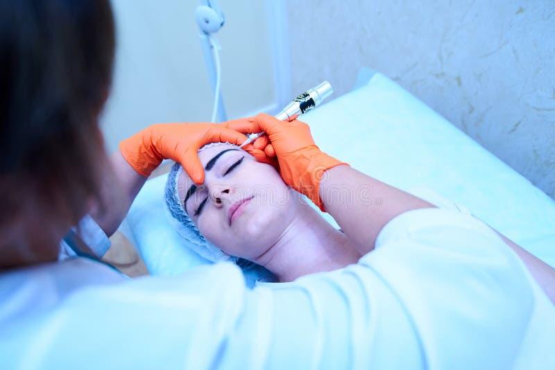O doutor nas luvas faz às sobrancelhas tattooing uma menina bonita que l imagens de stock royalty free