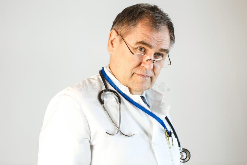 O doutor olha na distância, é vestido em uma veste branca e um estetoscópio pendura ao redor seu pescoço foto de stock