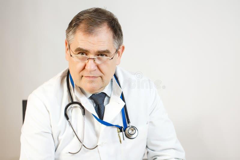 O doutor olha na frente dele, está vestindo um revestimento branco e um estetoscópio foto de stock royalty free