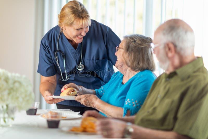 O doutor ou a enfermeira ?til Serving Senior Adult acoplam uma refei??o fotografia de stock