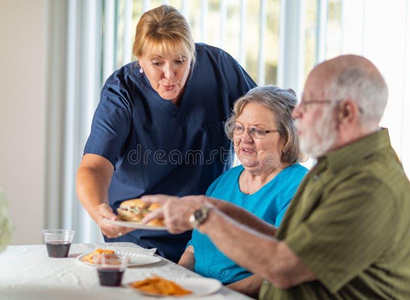 O doutor ou a enfermeira agrad?vel Serving Senior Adult acoplam uma refei??o fotografia de stock royalty free