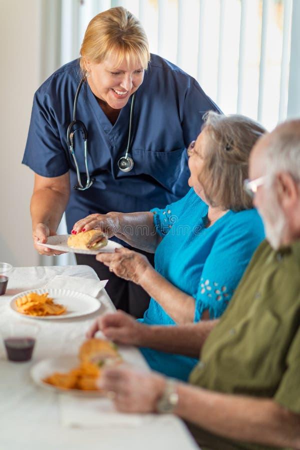 O doutor ou a enfermeira amig?vel Serving Senior Adult acoplam uma refei??o foto de stock