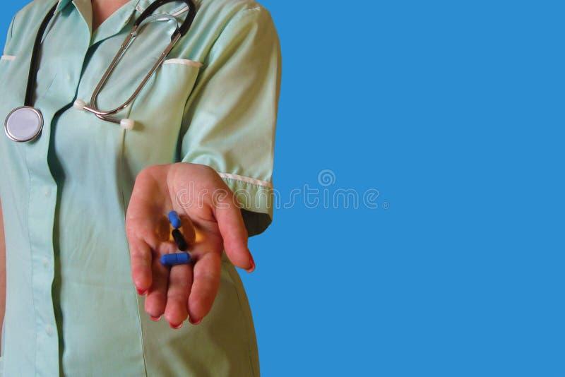 O doutor ou a enfermeira dão comprimidos Farmacêutico com tabuletas à disposição mulheres que dão o medicamento na clínica, na fa imagem de stock