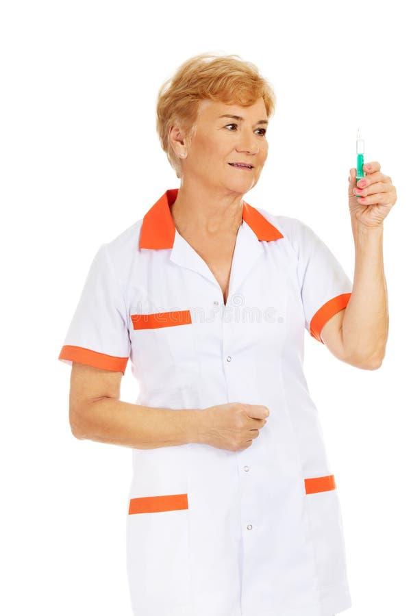 O doutor ou a enfermeira fêmea idosa do sorriso guardam a seringa imagens de stock royalty free