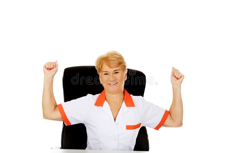 O doutor ou a enfermeira fêmea idosa feliz que sentam-se atrás do withd da mesa entregam acima foto de stock royalty free