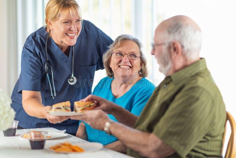 O doutor ou a enfermeira f?mea Serving Senior Adult acoplam sandu?ches em fotos de stock
