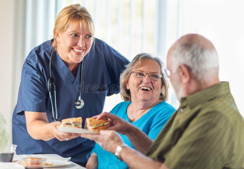 O doutor ou a enfermeira f?mea Serving Senior Adult acoplam sandu?ches fotografia de stock