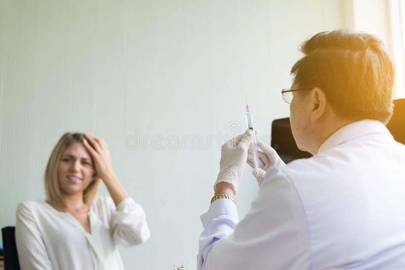 O doutor prepara a doação da vacina ao paciente assustado da jovem mulher com injeção ou à seringa no hospital fotos de stock royalty free