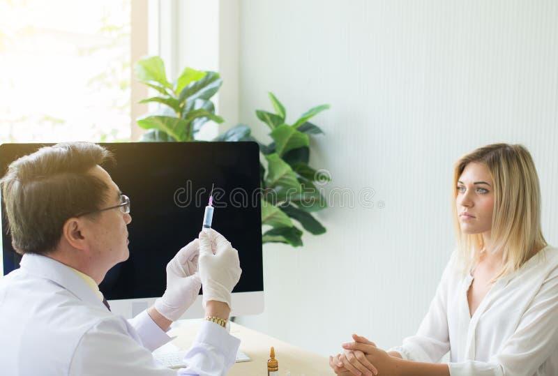 O doutor prepara a doação da vacina ao paciente da mulher com injeção ou à seringa na sala de hospital fotos de stock