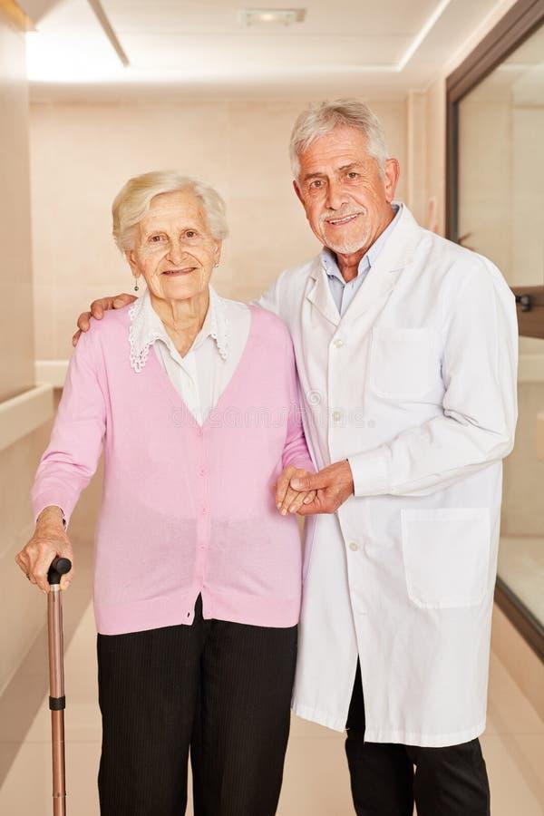 O doutor principal toma da mulher adulta com muleta imagens de stock royalty free