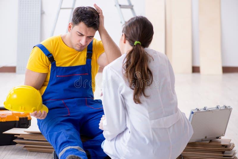 O doutor que ajuda o trabalhador ferido no canteiro de obras foto de stock